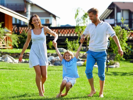 Mutter, Vater, Kind auf einer Wiese vor dem Ferienhaus
