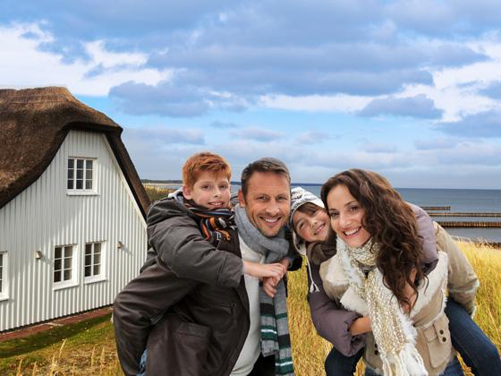 Familie im Winter vor einem Ferienhaus an der Nordsee