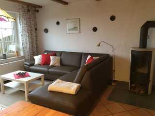 Ferienhaus Haus Blauort - SORGENFREIES REISEN* Wohnzimmer mit Terrassenzugang, Kamin und Küche...