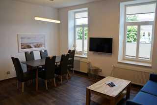 Kurhaus Nordstrand - exklusive Ferienwohnung 45494 Wohnzimmer mit Sitzecke (Schlafsofa) und Essecke