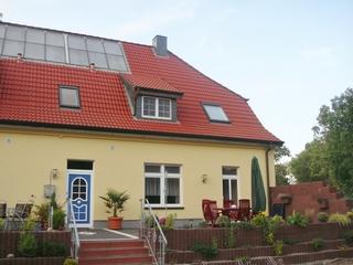 Ferienwohnung Am Schloßteich (Braun) - Sorgenfrei buchen Außenansicht mit möblierter Terrasse