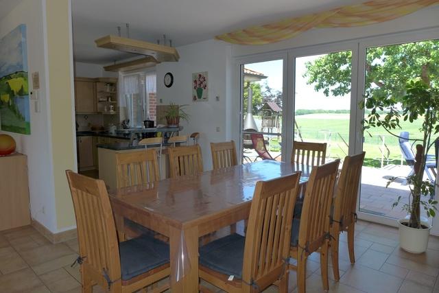Esstisch mit Blick auf den Garten und die Küche