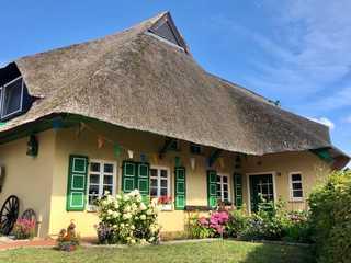 Im Reetdachhaus Hausansicht des reetgedeckten Hauses mit der FW...